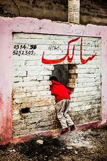 ein Junge schaut durch ein Loch in einer Mauer