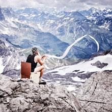 Foto: Mann auf mobiler Toilette vor Panorama