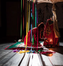 Szenenfoto: Delaine Le Bas vor einem Altar