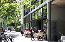 Foto: Menschen in der Sonne auf den Stühlen vor einem Restaurant, Fahrräder